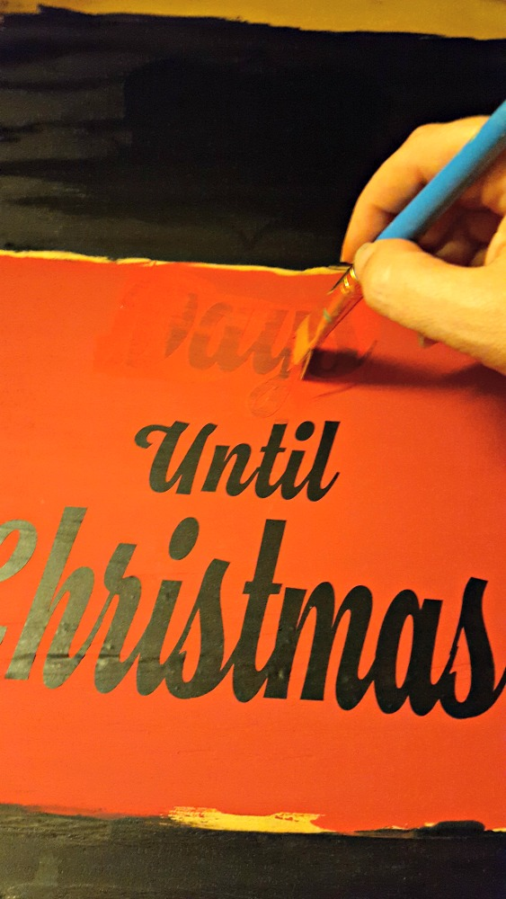painting a christmas sign with red paint