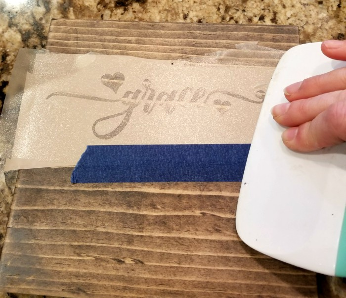 applying stencil to wood with transfer paper