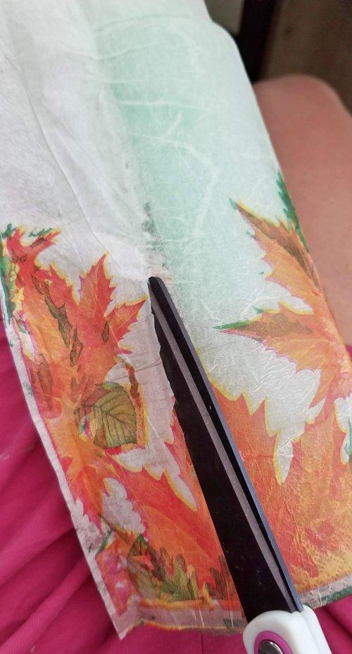 cutting extra decoupaged napkin off vase