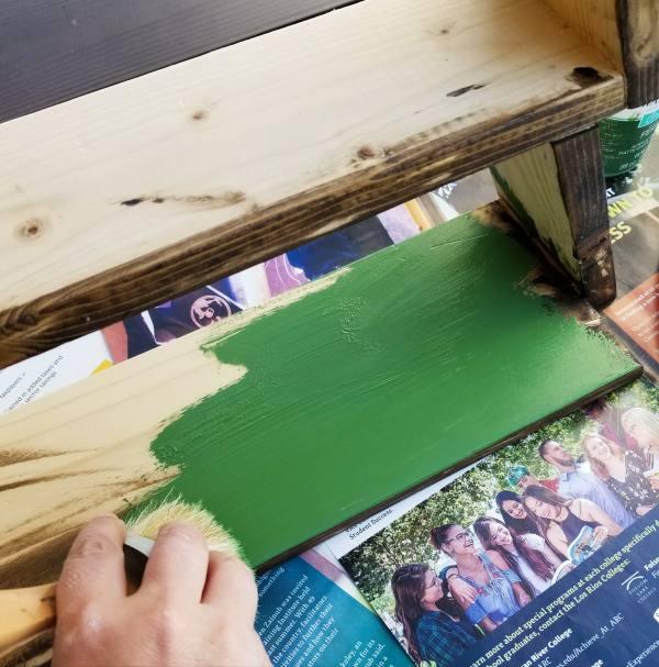 painting green chalk paint on wood shelf