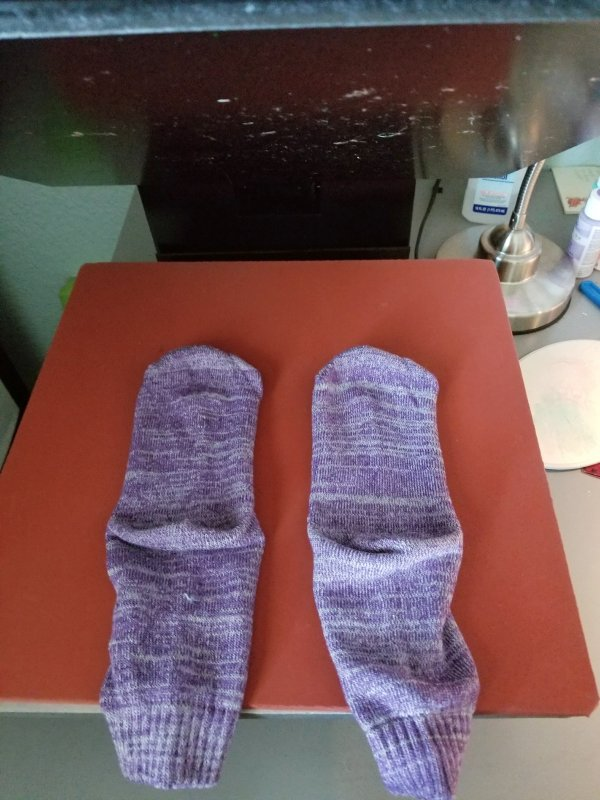applying iron-on to socks with heat press