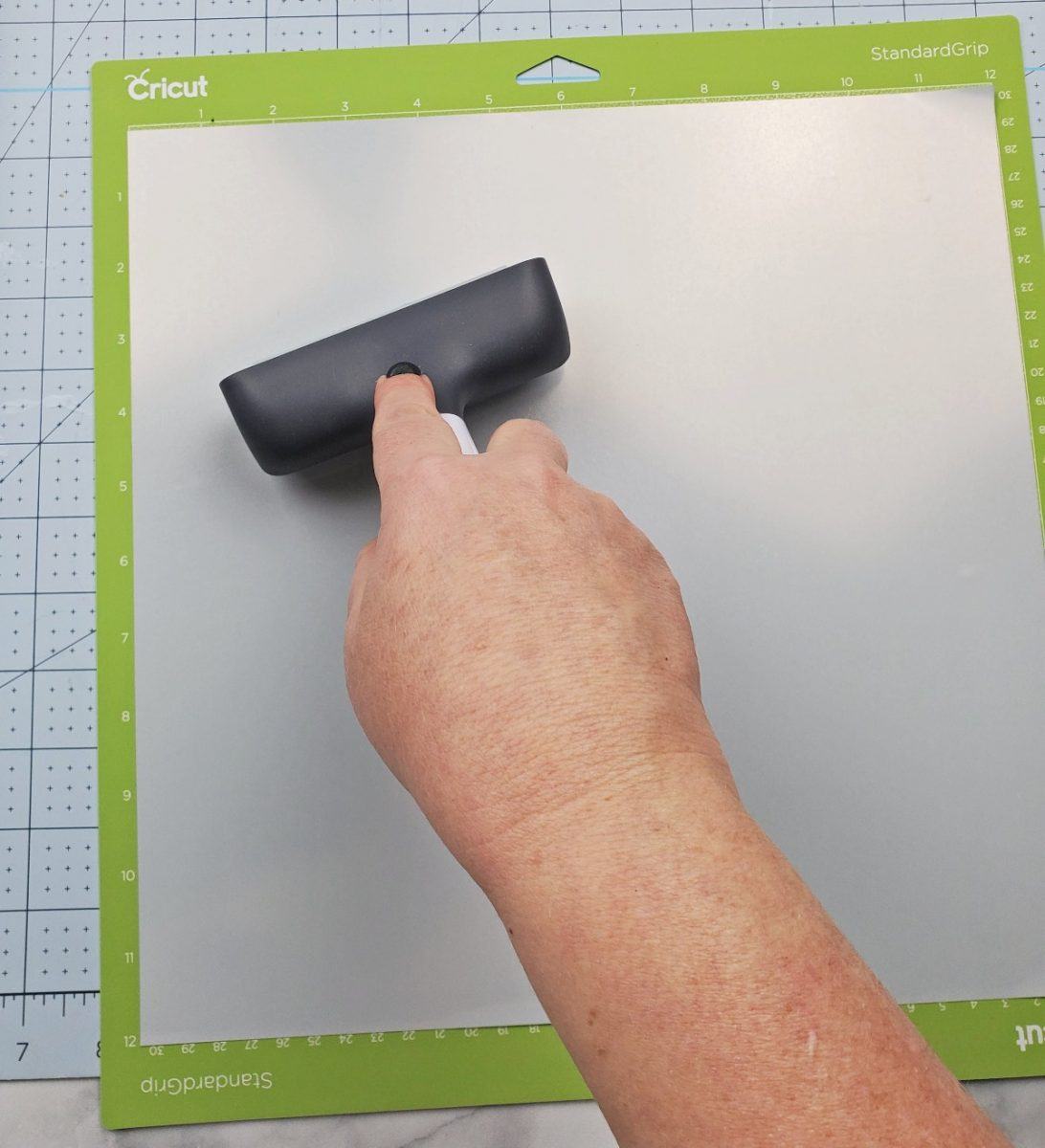 rolling down iron on vinyl on cricut mat