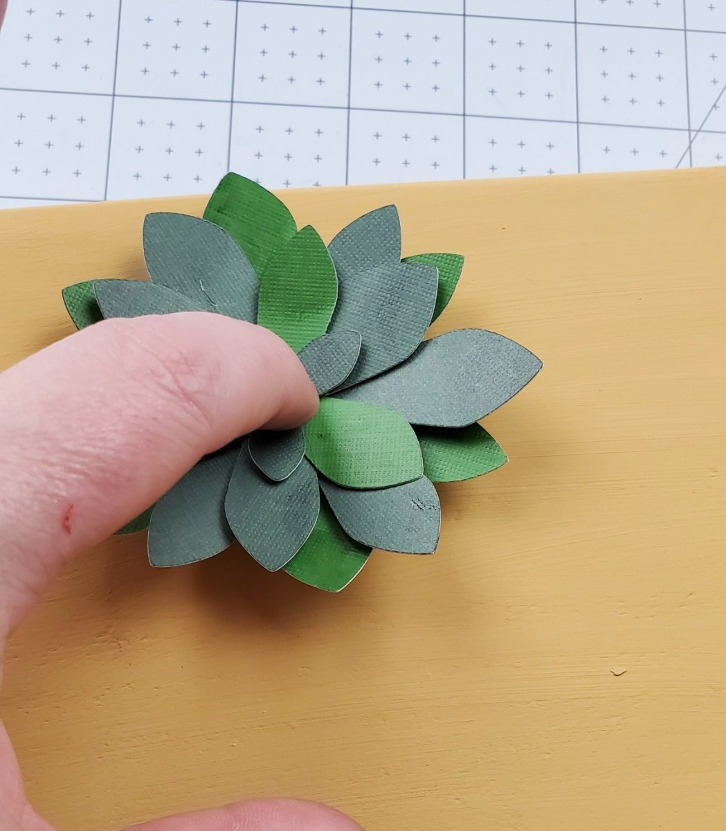 gluing paper flowers on wood