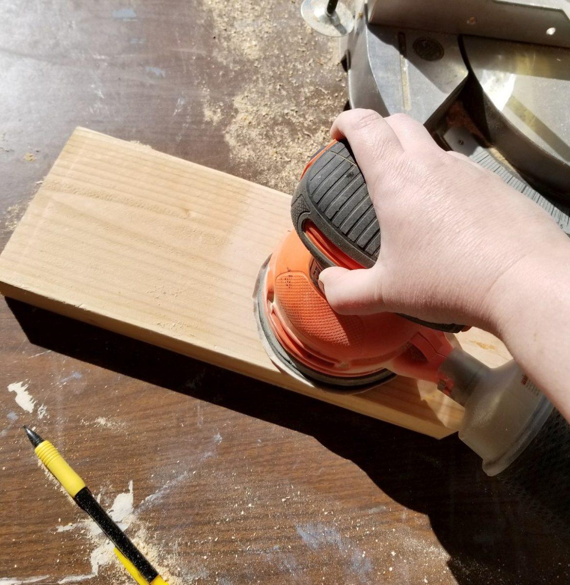sanding wooden pencil sign